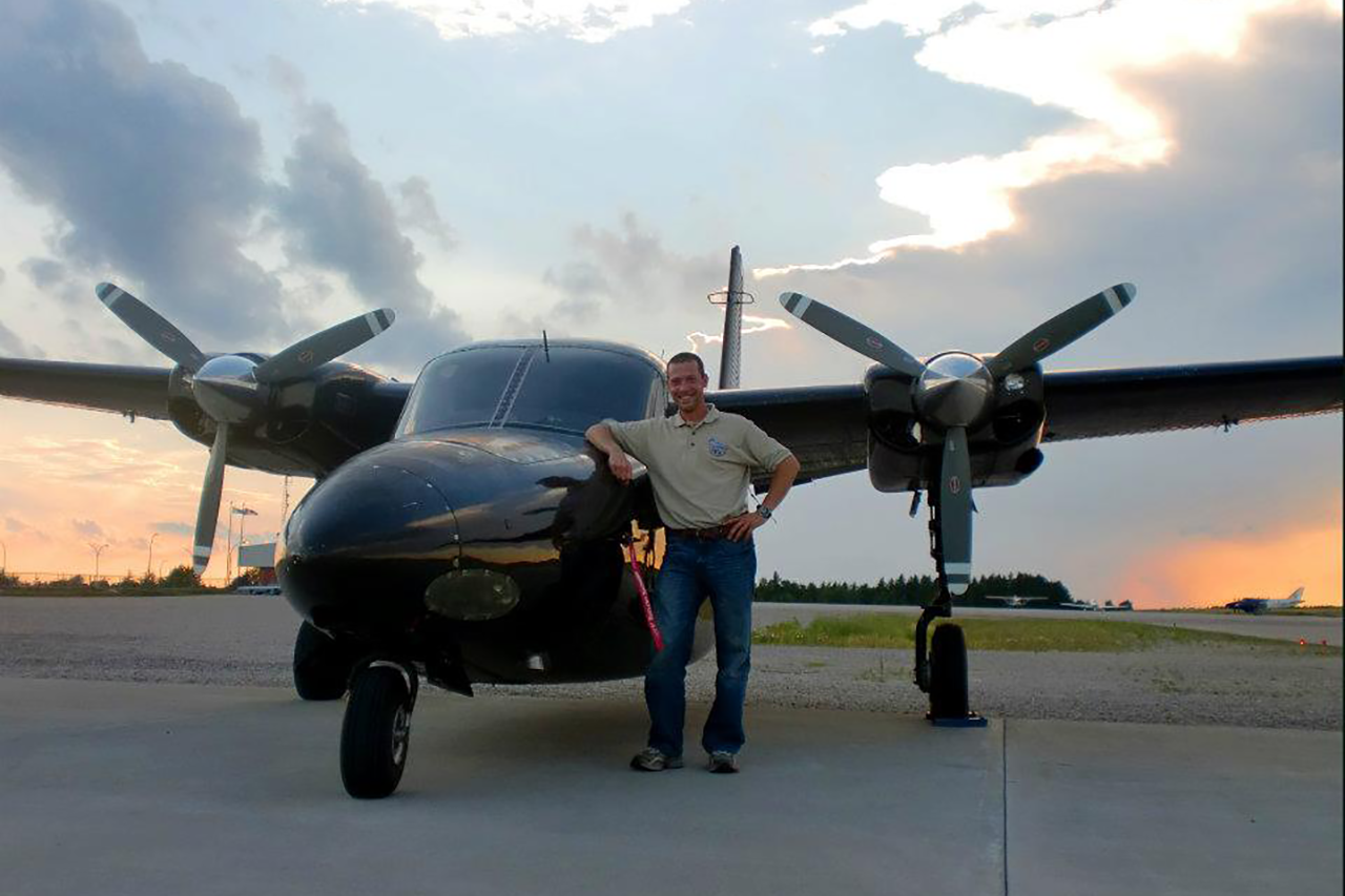 Man leaning on the nose of an airplane that is sitting on a runway