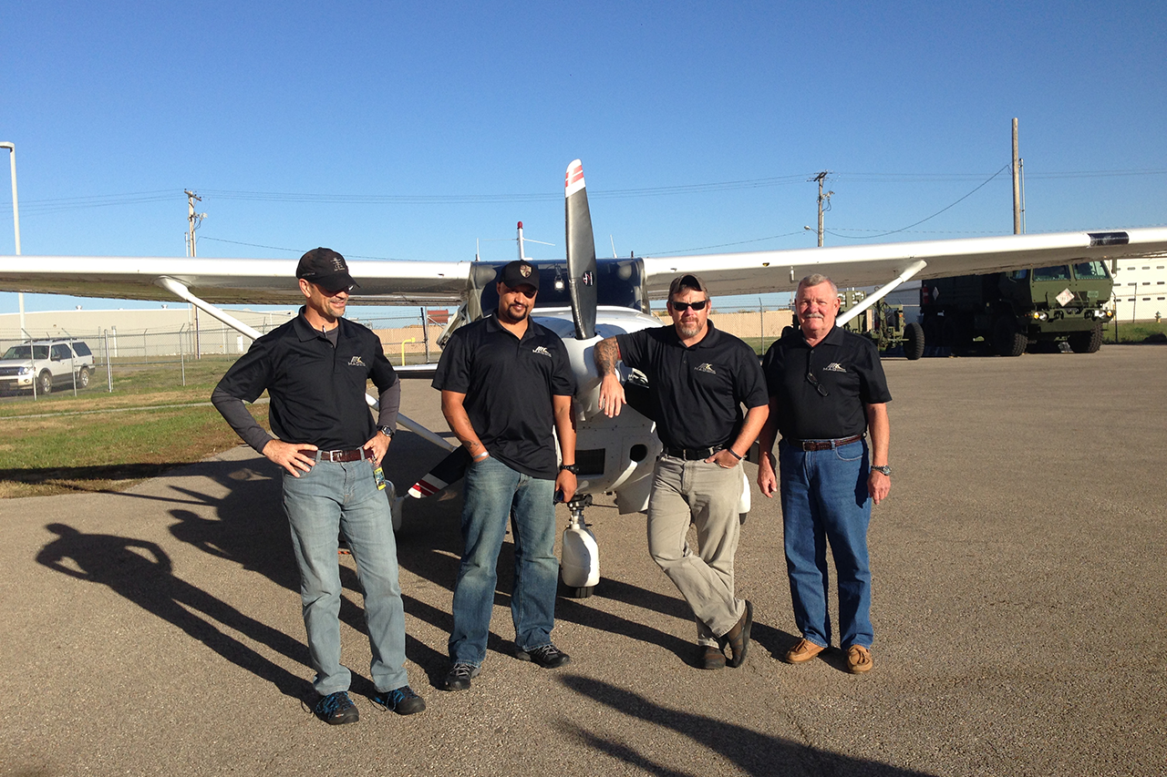 Four men posing in front of a small airplane