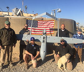 Men posing around an unmanned plane