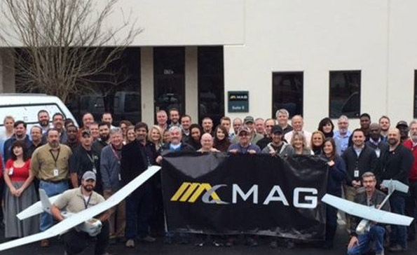 Large group of employees posing behind the MAG sign