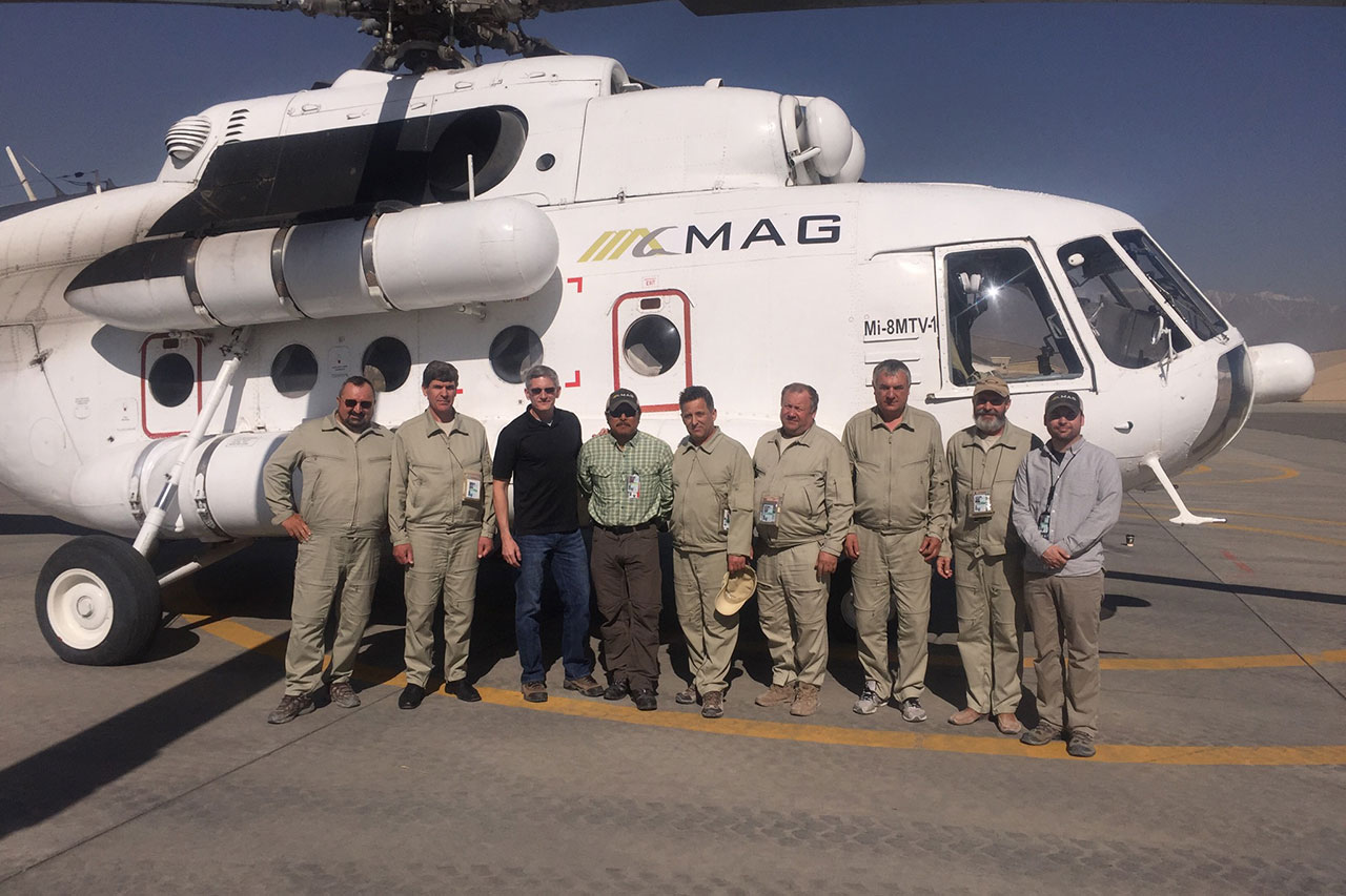 Men posing in front of a large helicopter
