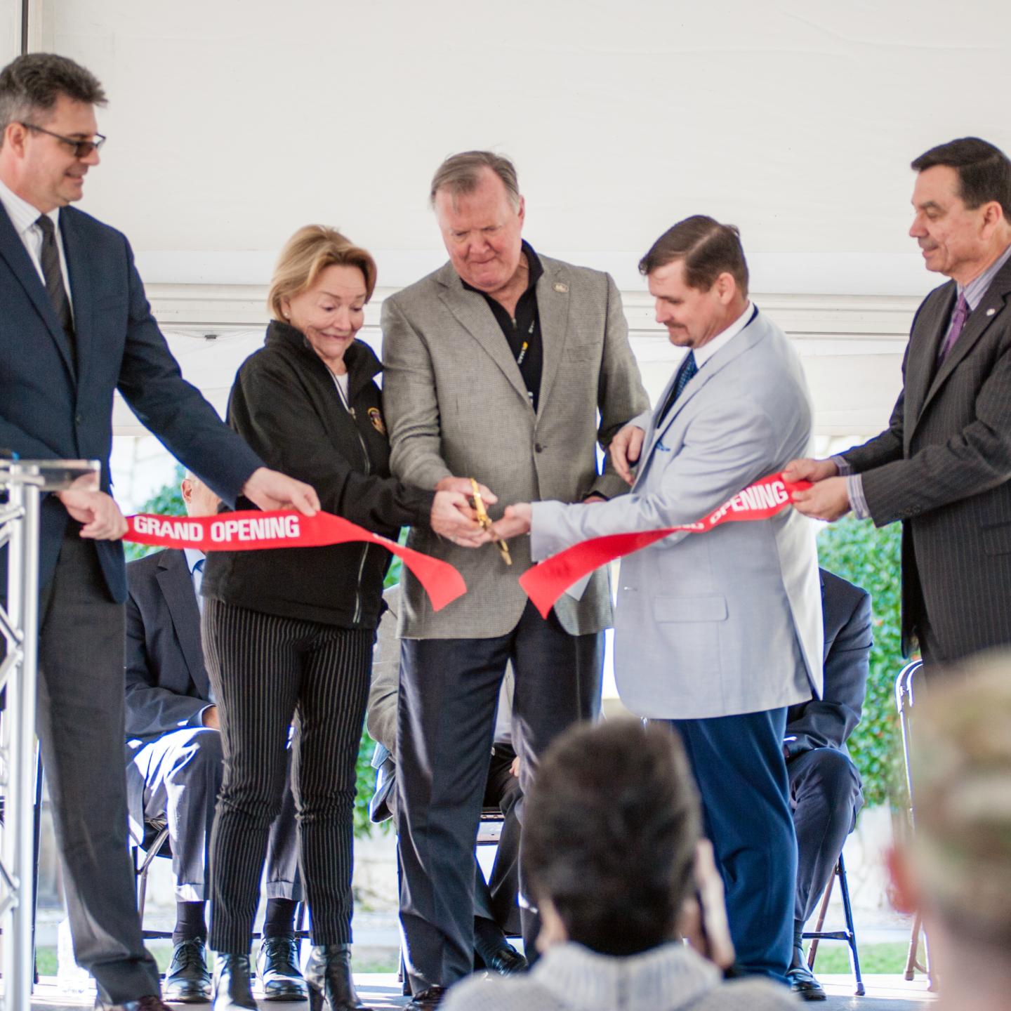 Group of people cutting the red ribbon to open a facility
